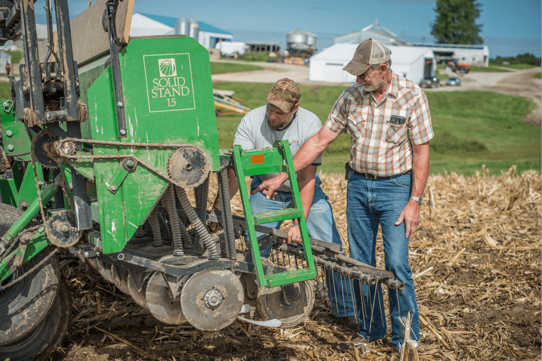 Roger Zylstra and son Wesley inspecting a no-till drill on their Central Iowa farm