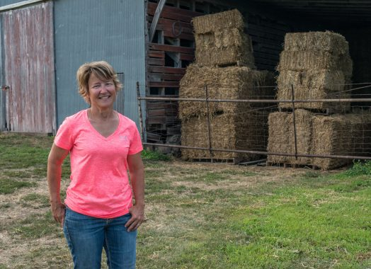 Angela Knuth standing in front of barn with straw