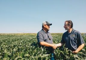 John Mesko and Keith Byerly shake hands in a field